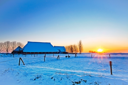 Sunset of farm in white winter landscape photo