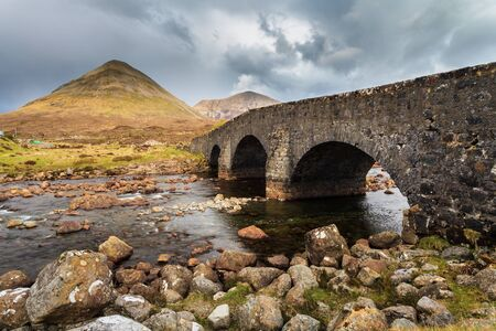 Ancient bridge at a river in a mountain landscape
