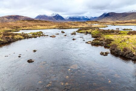 Calm river and snow covered mountains on the background photo