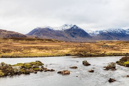 Calm river with snow covered mountains on the background photo