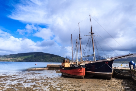 Boats in the harbour lying in the mud Stock Photo