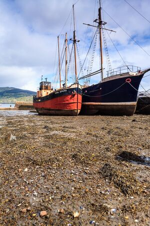 wheater: Boats lying in the mud in the harbour