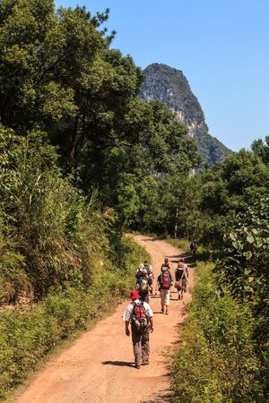 Group of people walking through limestone rock valley in South China photo