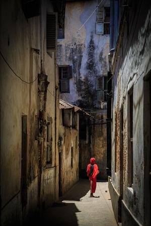 Veiled woman walking through a narrow street at Zanzibar photo