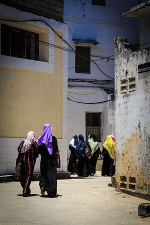 Veiled women walking through a city street at Zanzibar photo