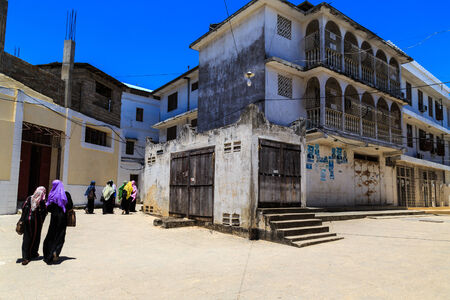 Veiled women walking through a city street at Zanzibar