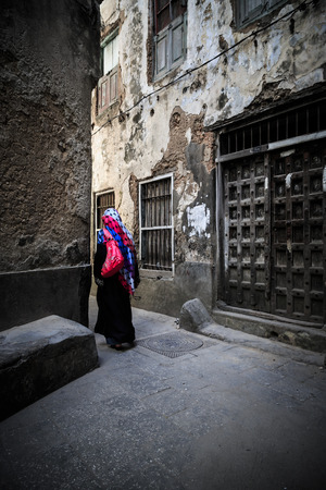 Veiled woman walking through a narrow street at Zanzibar