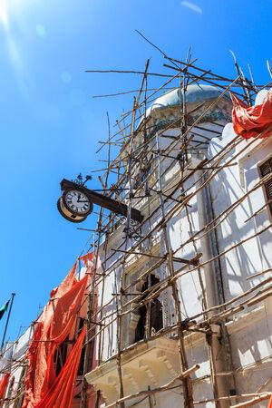 colonial building: Reloj colonial colgando de un viejo edificio colonial en Stone Town, Zanz�bar