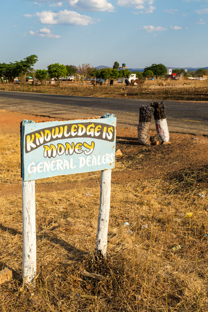 Road sign with charcoal bags along the road in africa, Tanzania