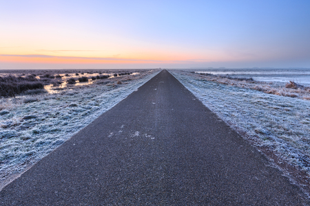 Desolate road in a winter rural landscape in Holland photo