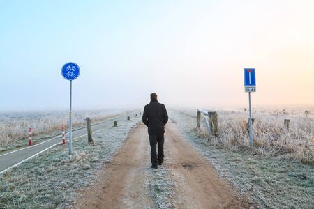 Man walking on a sand road in a winter landscape in the Netherlands Stock Photo