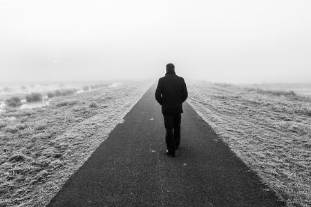 hombre solitario: Hombre caminando lejos en un raod desolado vac�o Foto de archivo