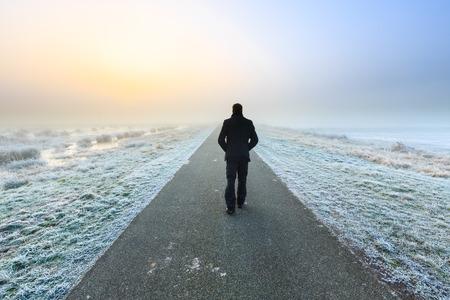 hombre solo: Hombre caminando lejos en un raod desolado vacío Foto de archivo
