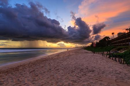 beach rain: Sea  and beach with dark rain clouds at sunset in the tropics