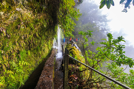 Waterfall falling on the walking trail along a levada in the mountains of Madeira, Portugal on a rainy day