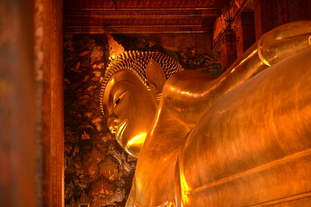 The Big golden Reclining Buddha within Wat Pho is the important temple in Bangkok, Thailand  photo