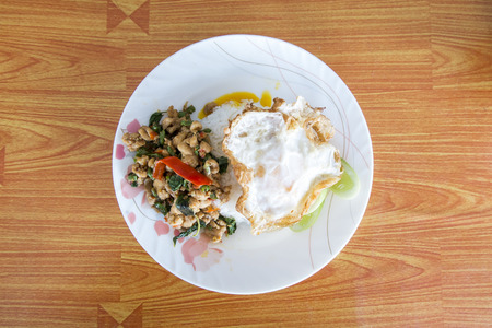 Spicy ground meat over rice with sauteed chopped, fresh chili and garlic, bell pepper, basil leaf, fried egg and cucumber photo