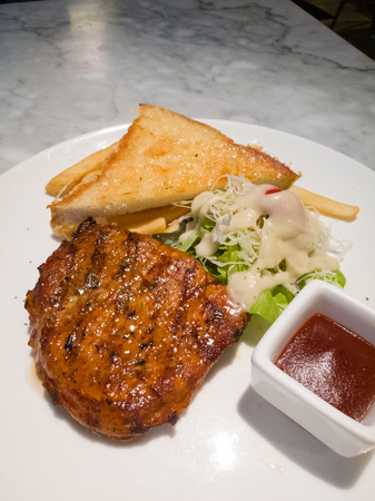 Pork chop steak in white plate. Including bread and vegetables