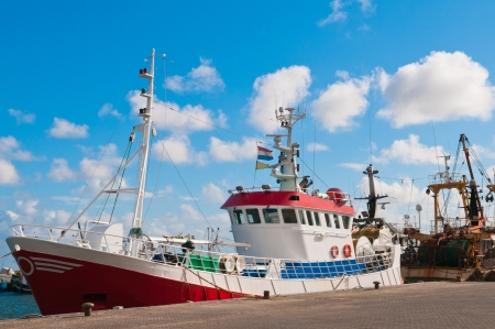 commercial fishing: red shrimp trawler in the harbor and blue sky Stock Photo