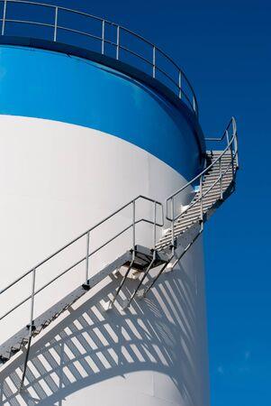 refiner�a de petr�leo: mantenimiento de la escalera en un tanque de almacenamiento de aceite Foto de archivo