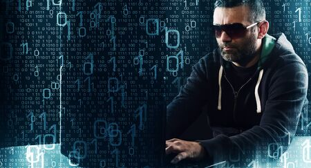 programmer computer: Hacker typing on laptop computer keyboard binary code background