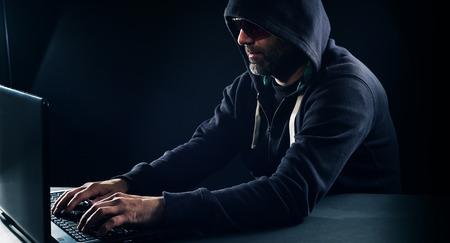 internet security: Hacker typing on laptop computer keyboard, black background