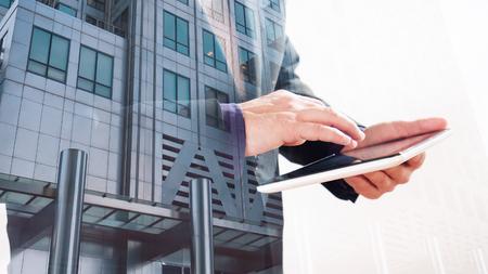 タブレット画面、白い背景に触れる実業家と二重露光のオフィスビル 写真素材