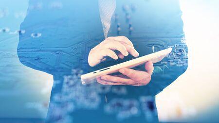 electronic background: Hi-tech concept, man using tablet on electronic background double exposure