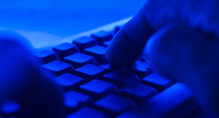 cybercrime: Criminal buying in dark net. POV man typing on keyboard