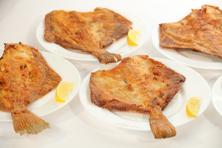 Fried flat fish on white plates and lemons