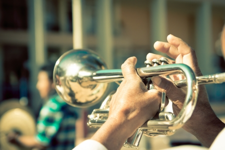 jazz: street band playing, selective focus on the hands with trumpet