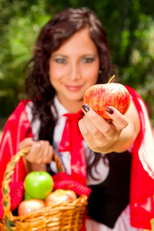 Little Red Riding Hood offering you an apple Stock Photo - 15654283