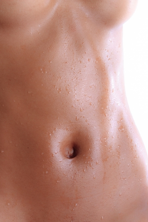Wet abdomen of a black nude young woman