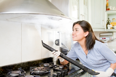 Young woman cleaning kitchen photo