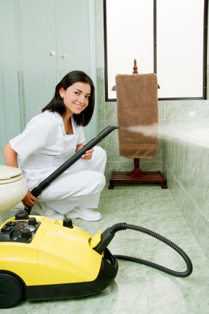 hogging: Young woman steam cleaning the bathroom Stock Photo