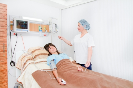 check room: doctor or nurse talking to patient in hospital Stock Photo