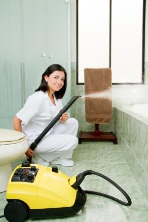 mujer limpiando: Profesional se�ora de la limpieza limpio bathrooom Foto de archivo