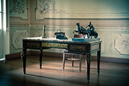Old writing desk full of quills and typewriter photo