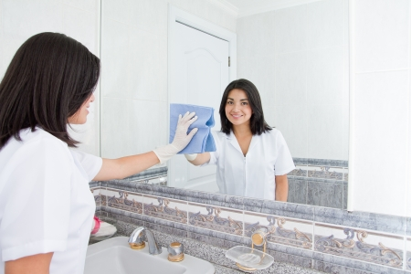 Pretty woman cleans  mirror in bathroom at home