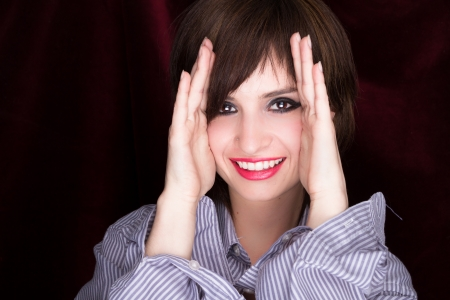 shyness: Woman with hands against cheeks, black background