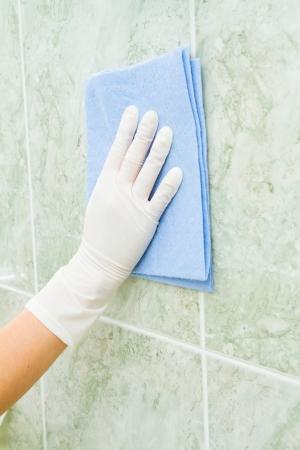 Ménage de sexe féminin, nettoyage carreaux avec des gants