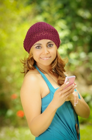 Young Woman with smartphone, green background photo
