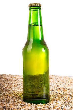 Beer and beach sand, studio shot photo