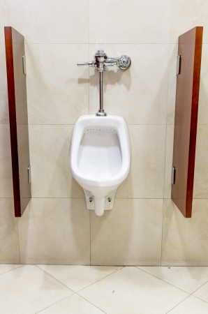Public urinal over tiled wall photo