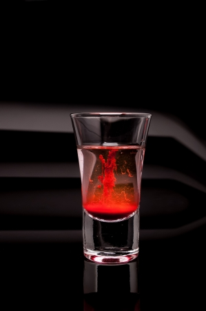 red shot glass on a dark background