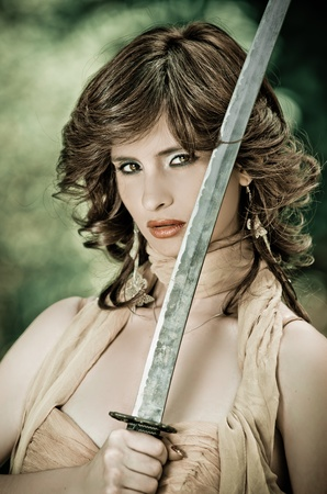 Gorgeous young woman holding a sword in the park photo