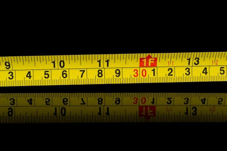 millimetres: Tape measure in millimetres and inches on black Stock Photo