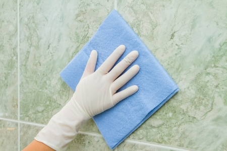 female hand cleaning kitchen tiles with sponge photo