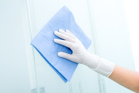 scrubbing up: Hand and glove  with blue sponge cleaning glass Stock Photo