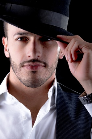 Hhandsome young man with a hat black background photo